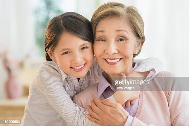 USA, New Jersey, Jersey City, Granddaughter (8-9) embracing grandmother