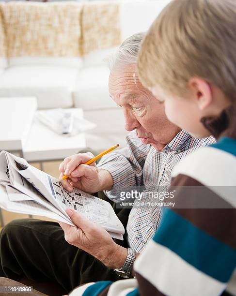 USA, New Jersey, Jersey City, grandfather and grandson (8-9) doing crossword