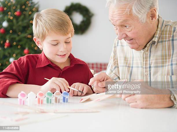 USA, New Jersey, Jersey City, grandfather and grandson (8-9 years) painting model airplane