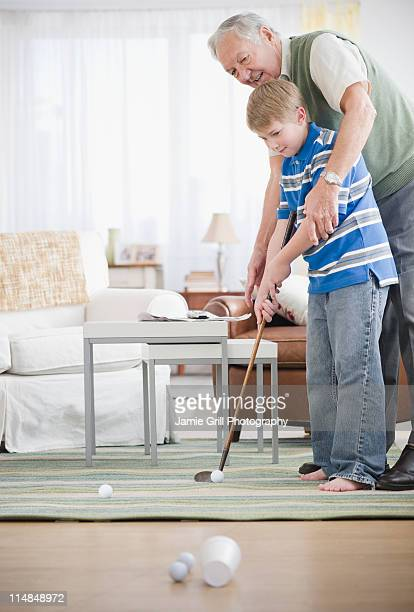USA, New Jersey, Jersey City, grandfather and grandson (8-9) playing golf at home
