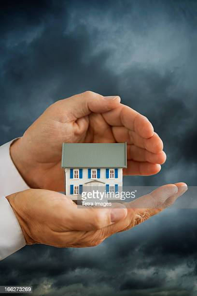 USA, New Jersey, Jersey City, Hands holding model house in front of stormy sky
