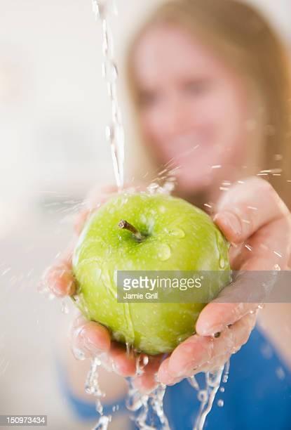 USA, New Jersey, Jersey City, Hands washing green apple