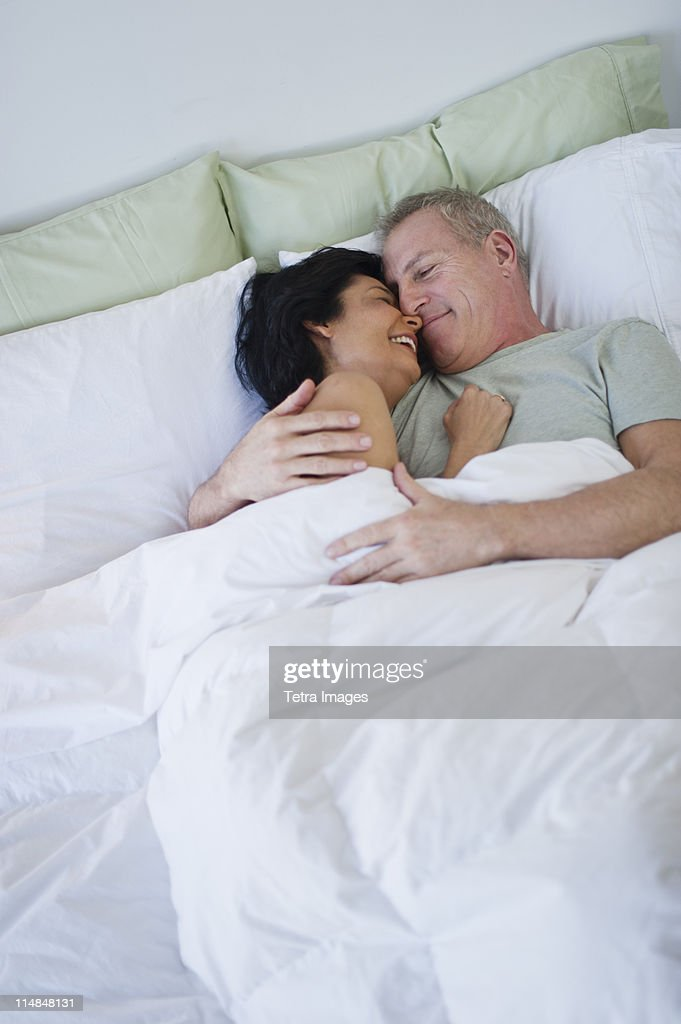 usa new jersey jersey city happy mature couple laying in bed stock photo getty images. Black Bedroom Furniture Sets. Home Design Ideas