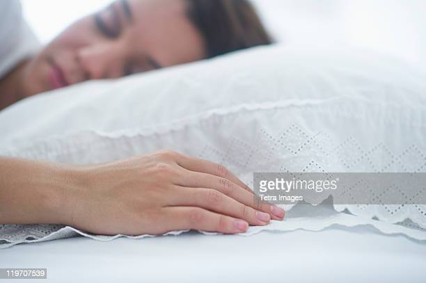 USA, New Jersey, Jersey City, Happy young woman sleeping in bed
