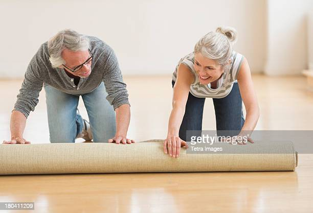 USA, New Jersey, Jersey City, Man and woman rolling carpet