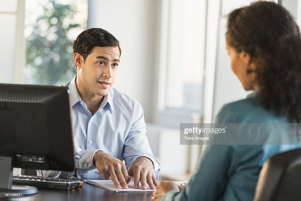 USA, New Jersey, Jersey City, Man and woman talking at desk during job interview : Stock Photo