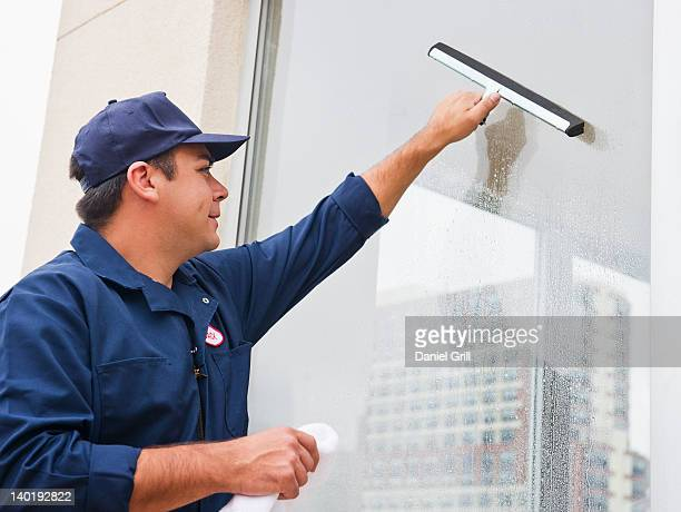 USA, New Jersey, Jersey City, Man cleaning window