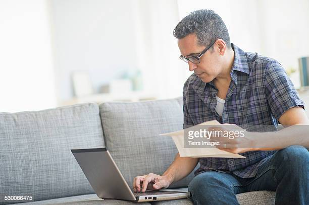 USA, New Jersey, Jersey City, Man doing home finances with laptop