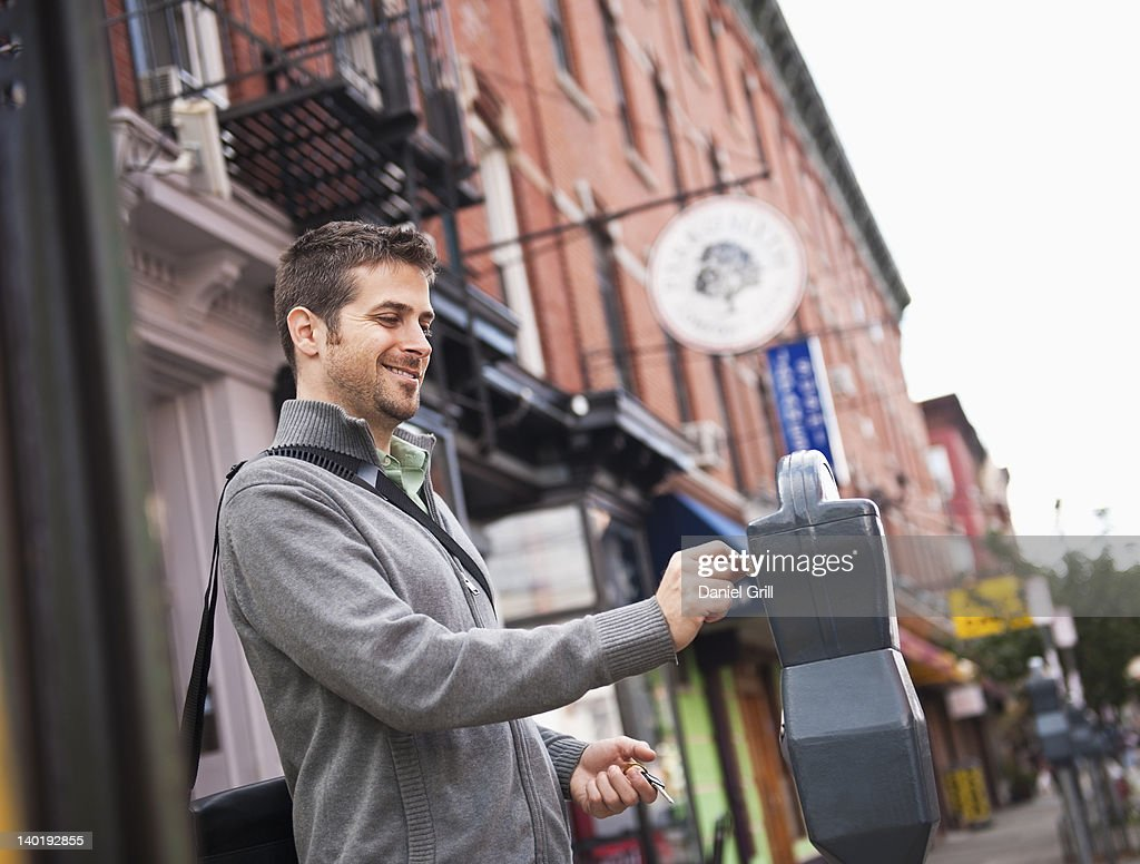 USA, New Jersey, Jersey City, Man inserting coin to parking meter