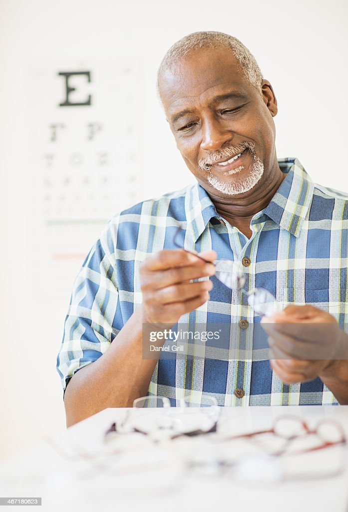 USA, New Jersey, Jersey City, Man looking at glasses in store