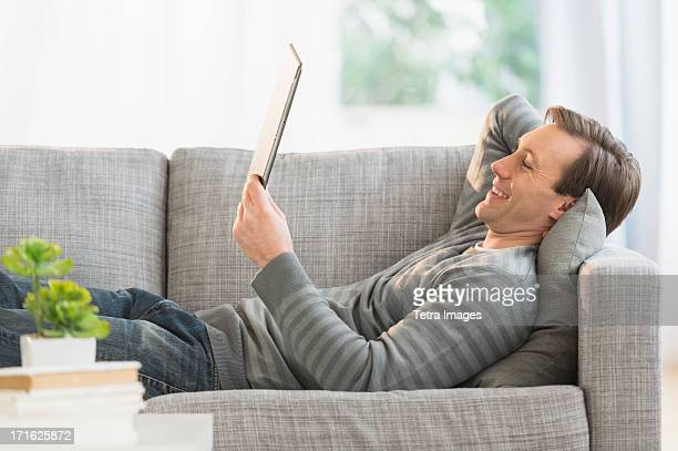 USA, New Jersey, Jersey City, Man lying on sofa watching tablet pc
