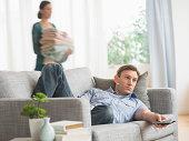 USA, New Jersey, Jersey City, Man lying on sofa watching tv