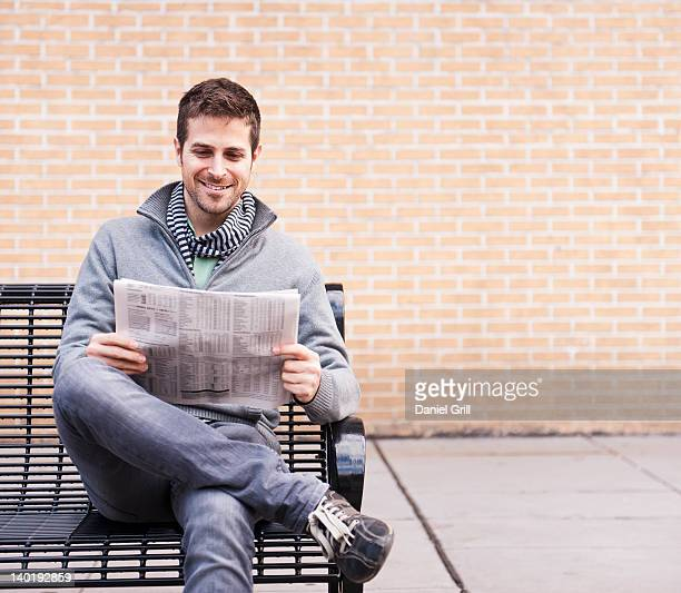 USA, New Jersey, Jersey City, Man on bench reading newspaper