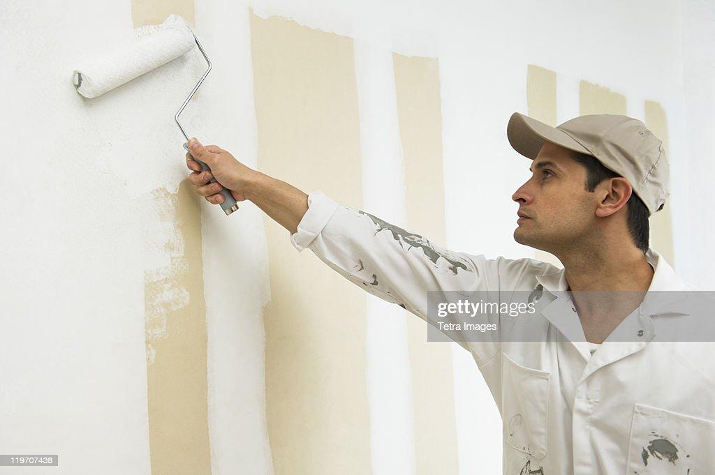 USA, New Jersey, Jersey City, man painting wall white