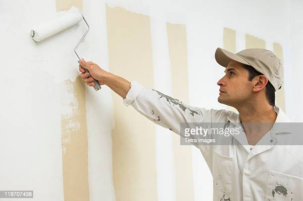 USA, New Jersey, Jersey City, man painting wall white