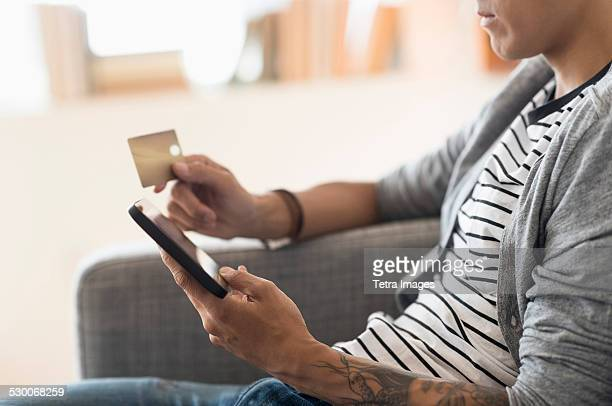 USA, New Jersey, Jersey City, Man paying with credit card on tablet