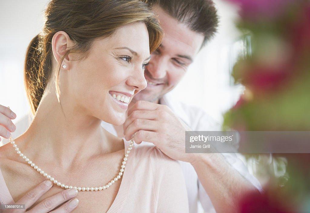 USA, New Jersey, Jersey City, Man putting pearls on his girlfriend's neck