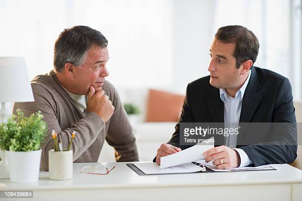 USA, New Jersey, Jersey City, Man talking with financial advisor in home