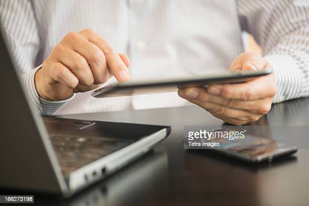 USA, New Jersey, Jersey City, Man using tablet pc, laptop and smartphone