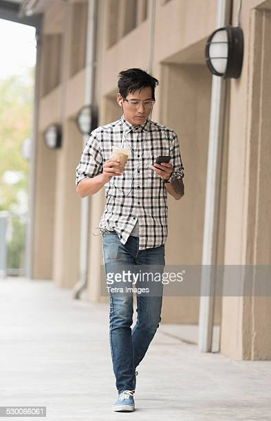 USA, New Jersey, Jersey City, Man walking on sidewalk with iced coffee and mobile phone