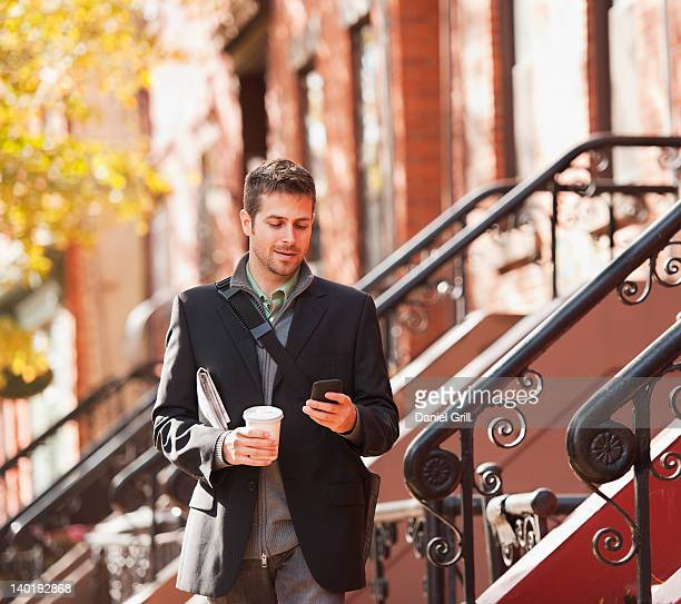USA, New Jersey, Jersey City, Man walking with mobile phone and coffee