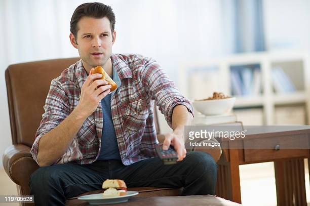 USA, New Jersey, Jersey City, man watching tv and eating sandwich