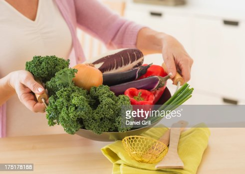 USA, New Jersey, Jersey City, Mature woman holding wok with vegetables : Stock Photo