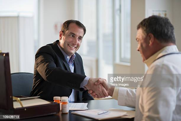 USA, New Jersey, Jersey City, Medical sales representative shaking hands with doctor in office