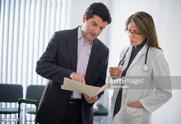 USA, New Jersey, Jersey City, Medical sales representative talking with female doctor in office