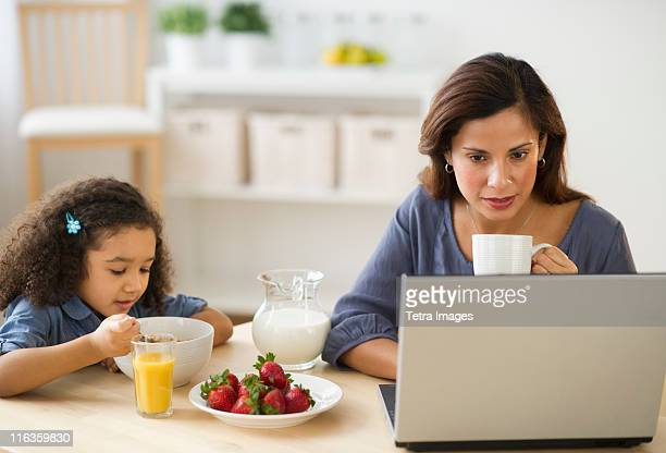 USA, New Jersey, Jersey City, mother and daughter (6-7) during breakfast