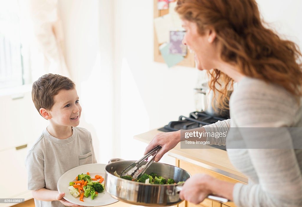 USA, New Jersey, Jersey City, Mother and son (6-7) serving healthy dinner