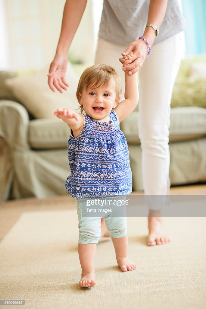 USA, New Jersey, Jersey City, Mother assisting baby daughter (18-23 months) with her first steps