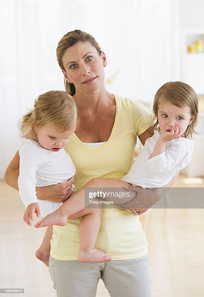 USA, New Jersey, Jersey City, Mother holding daughters (2-3) and making facial expression : Stockfoto