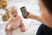 USA, New Jersey, Jersey City, Mother photographing her baby daughter (6-11 months) with mobile phone
