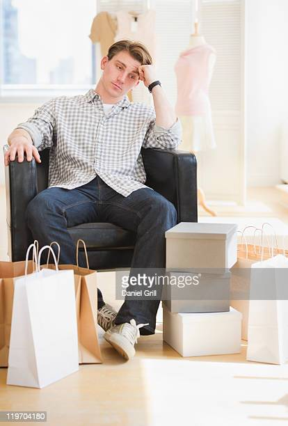 USA, New Jersey, Jersey City, pensive man sitting in clothes store