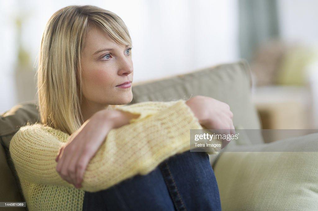 USA, New Jersey, Jersey City, Pensive woman sitting on sofa : Stock Photo