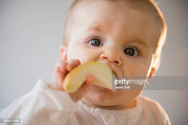 USA, New Jersey, Jersey City, Portrait of baby girl (6-11 months) eating apple