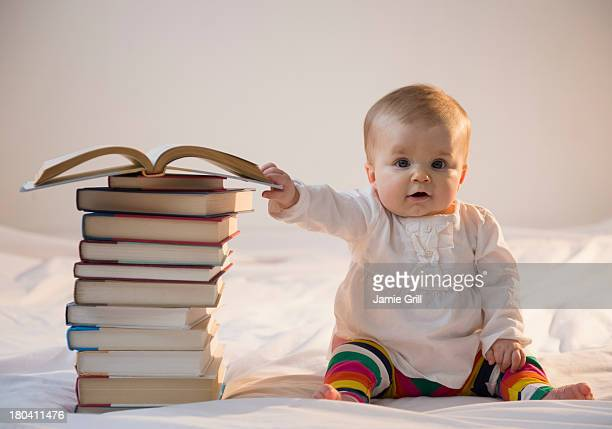 USA, New Jersey, Jersey City, Portrait of baby girl (6-11 months) sitting in bed with stack of books