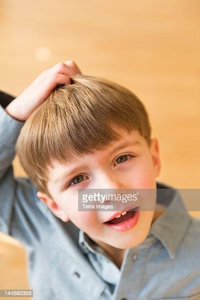 USA, New Jersey, Jersey City, Portrait of boy (4-5) scratching head