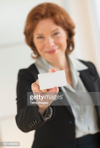 USA, New Jersey, Jersey City, Portrait of businesswoman holding blank business card : Stock Photo