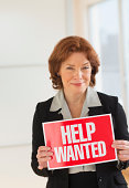 USA, New Jersey, Jersey City, Portrait of businesswoman holding help wanted sign