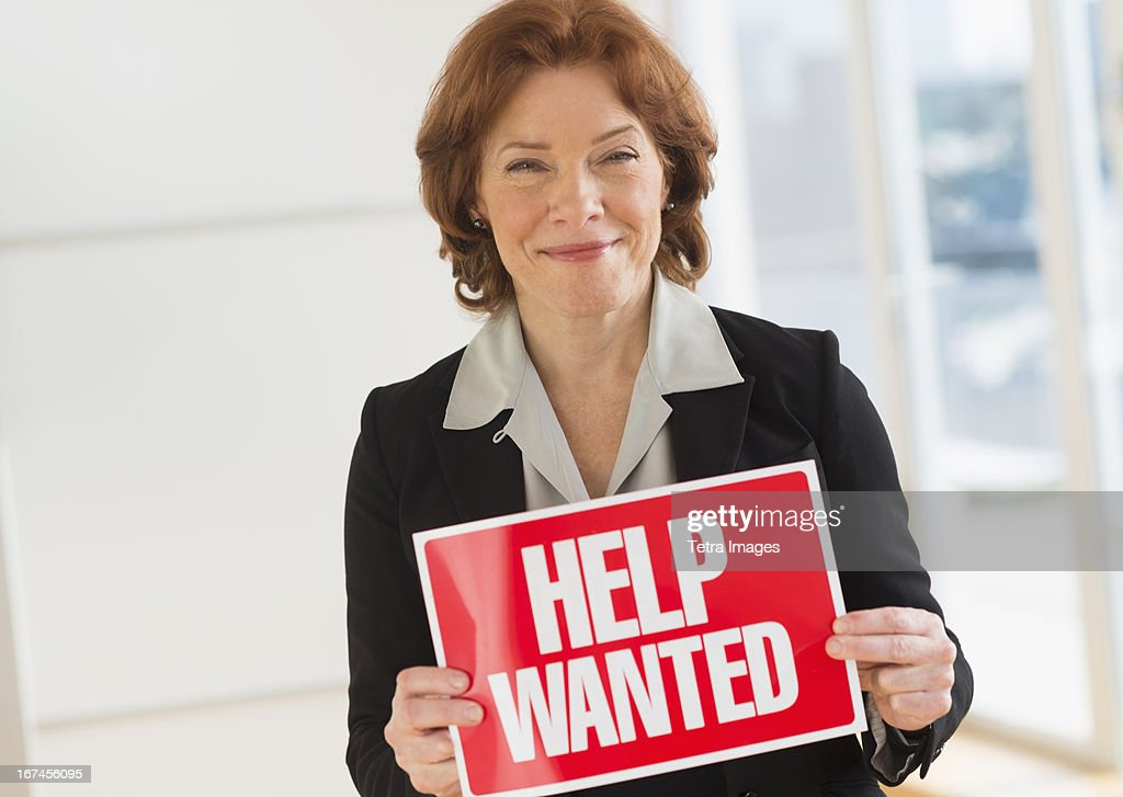 USA, New Jersey, Jersey City, Portrait of businesswoman holding help wanted sign : Stock Photo