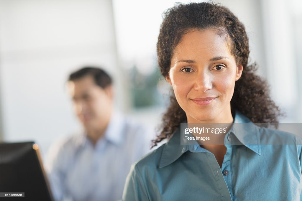 USA, New Jersey, Jersey City, Portrait of businesswoman in office with male executive working in background : Stock Photo