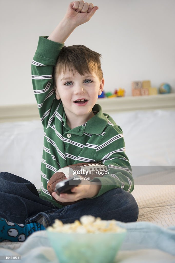 USA, New Jersey, Jersey City, Portrait of cheerful boy (4-5) sitting on bed, holding football : Stock Photo