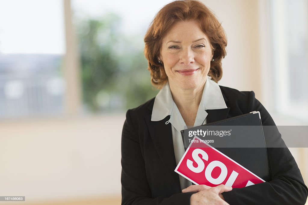 USA, New Jersey, Jersey City, Portrait of female real estate agent holding sold sign : Stock Photo