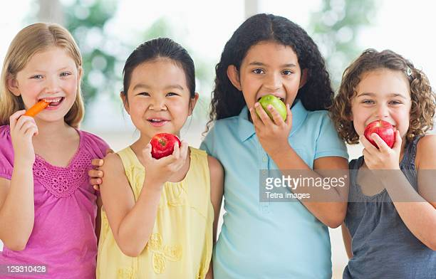 USA, New Jersey, Jersey City, Portrait of girls (6-9) eating fruits