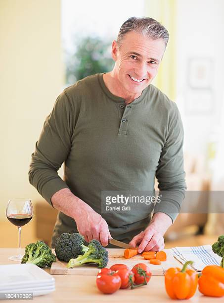USA, New Jersey, Jersey City, Portrait of man cutting vegetables