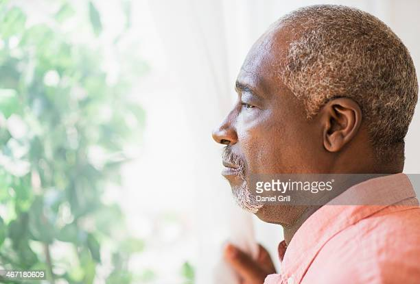 USA, New Jersey, Jersey City, Portrait of man looking through window