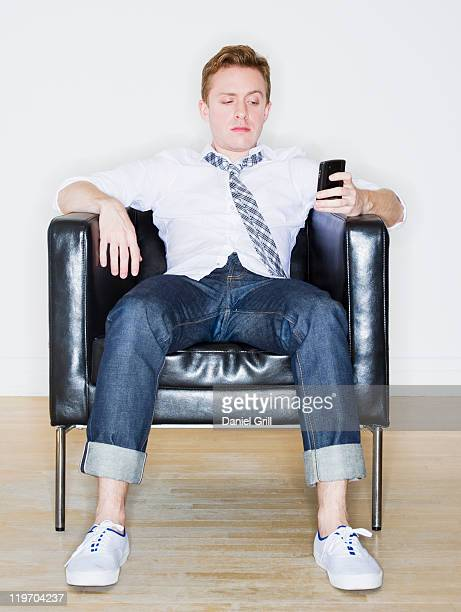 USA, New Jersey, Jersey City, portrait of man sitting in armchair using phone