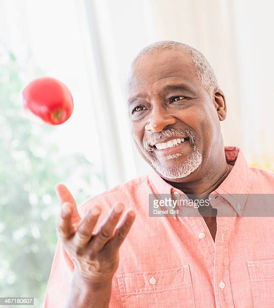 USA, New Jersey, Jersey City, Portrait of man throwing red apple